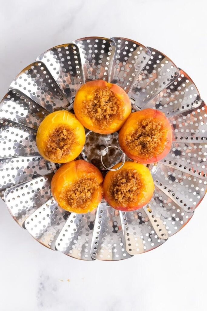 A steamer basket with 5 cooked stuffed peaches sitting on top of the steamer basket.