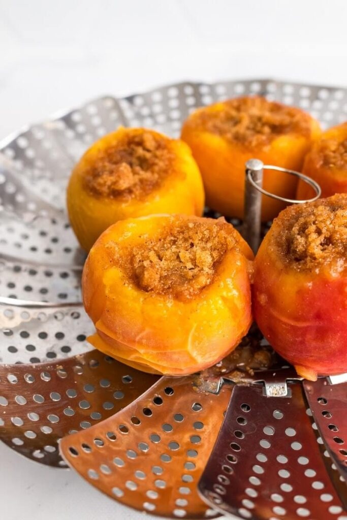A side view of a steamer basket with 5 cooked stuffed peaches sitting on top of the steamer basket.