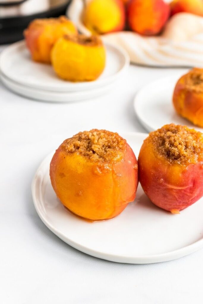 Cooked stuffed peaches sitting on plates, sitting next to fresh peaches on a kitchen towel and an Instant Pot.