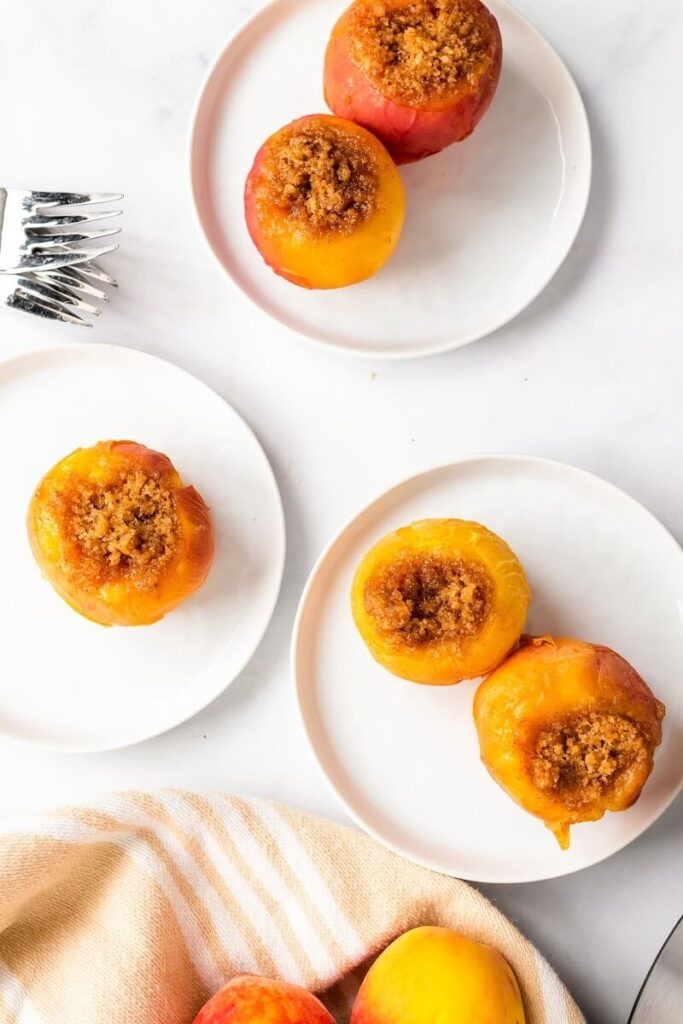 Overhead view of 3 plates with stuffed peaches, sitting next to forks and a kitchen towel with fresh peaches.