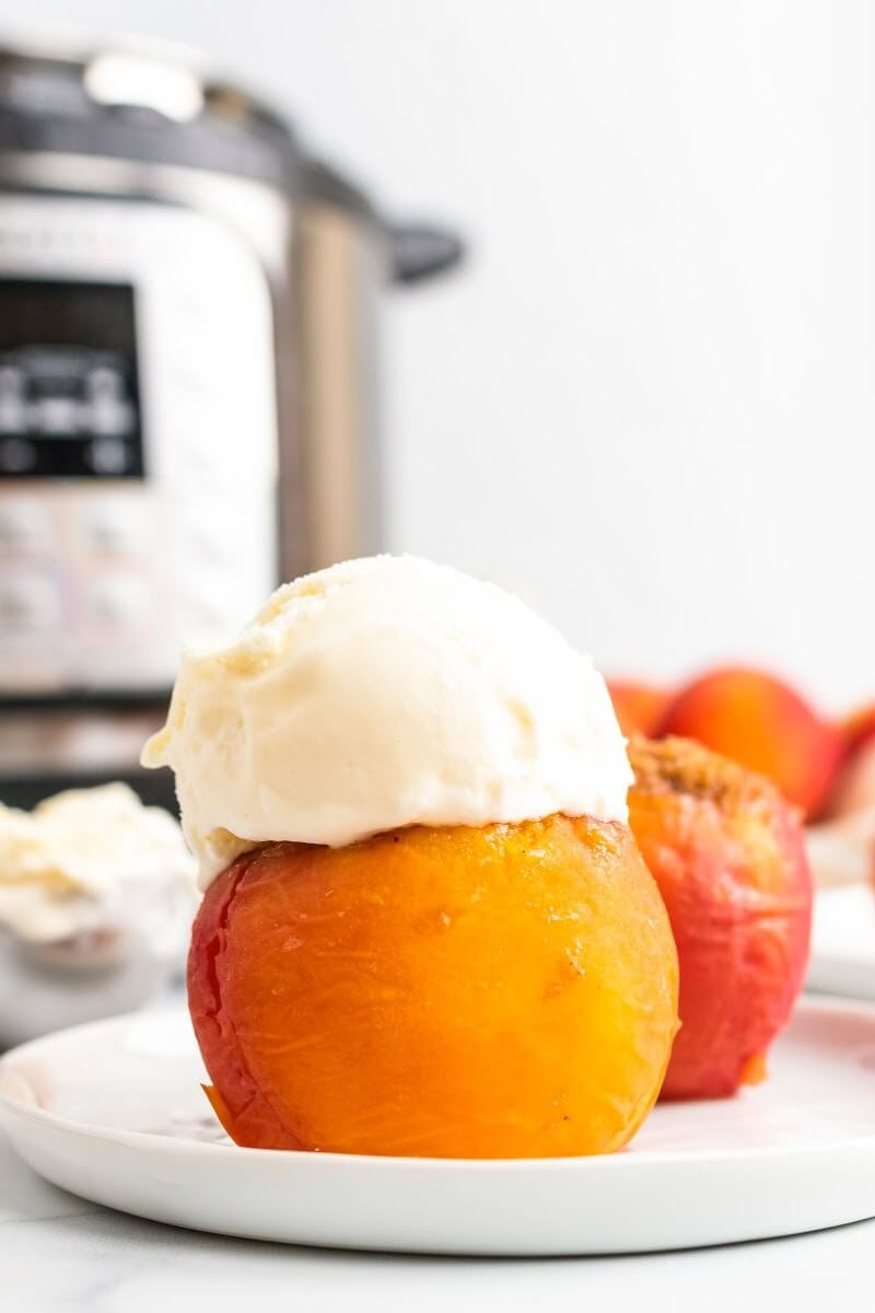Cooked stuffed peaches sitting on a plate, one topped with a scoop of vanilla ice cream, sitting next to fresh peaches, an ice cream scooper full of ice cream and an Instant Pot.