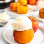 Cooked stuffed peaches sitting on plates, one topped with a scoop of vanilla ice cream, sitting next to fresh peaches, an ice cream scooper full of ice cream and an Instant Pot.