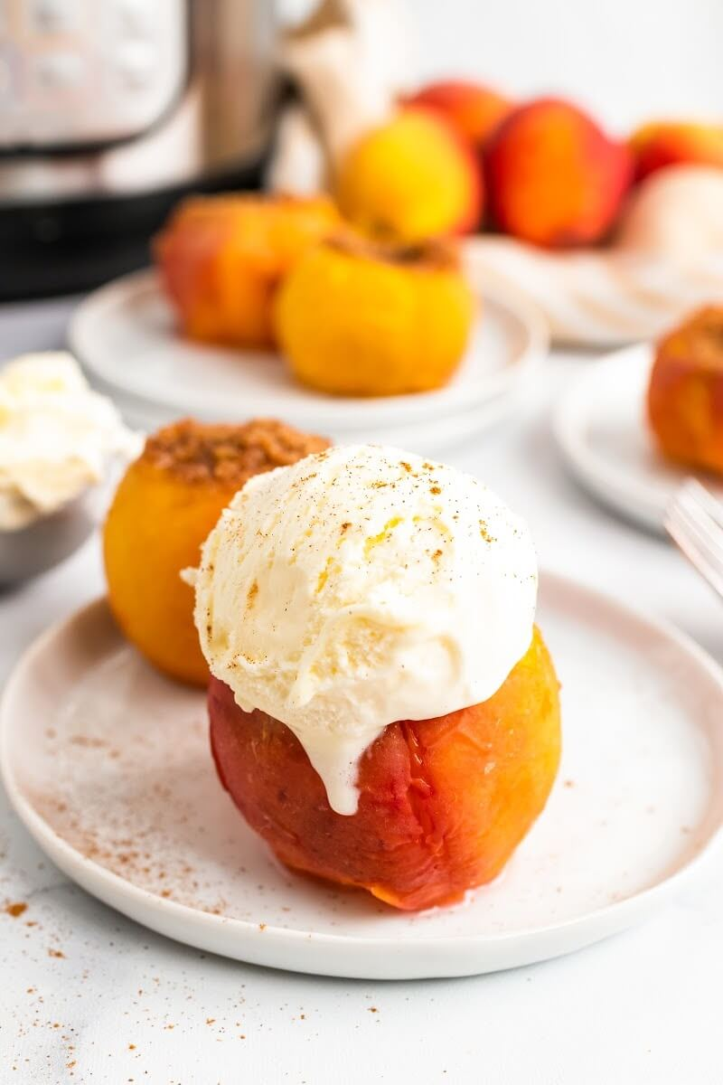 Cooked stuffed peaches sitting on plates, one topped with a scoop of vanilla ice cream dusted with ground cinnamon, sitting next to fresh peaches on a kitchen towel, an ice cream scooper full of ice cream and an Instant Pot.