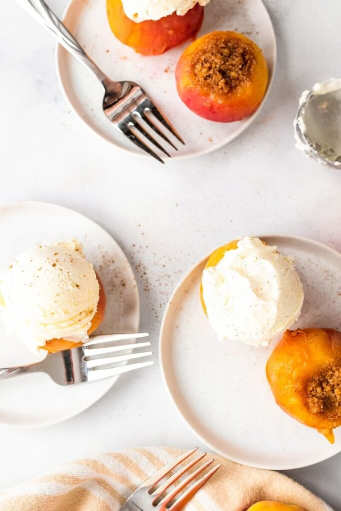 Overhead view of 3 plates with 2 stuffed peaches per plate, each plate has one stuffed peach topped with a scoop of vanilla ice cream dusted with ground cinnamon, sitting next to an ice cream scooper and 3 forks.