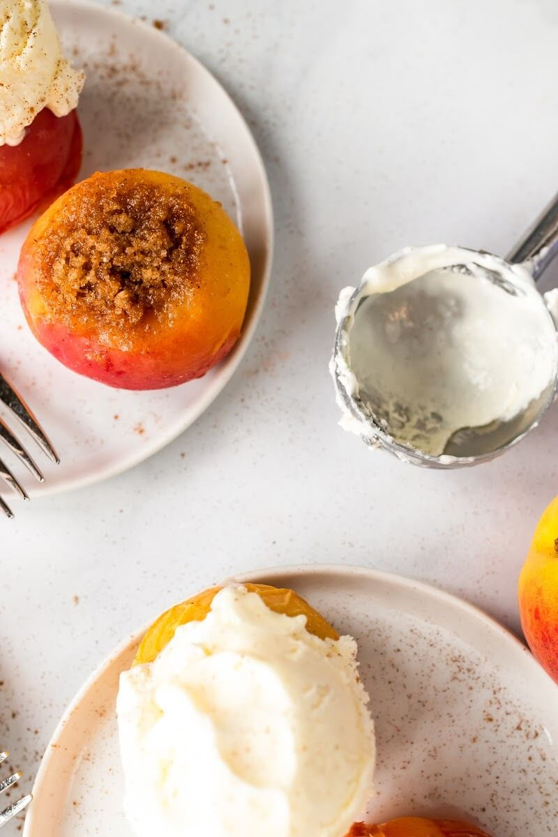 Two plates with 2 stuffed peaches per plate, each plate having one stuffed peach topped with a scoop of vanilla ice cream, sitting next to an ice cream scooper, forks and a fresh peach.