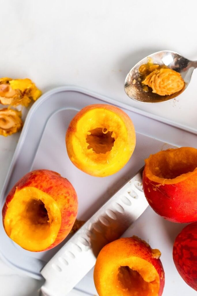A cutting board and knife with hollowed out fresh peaches with the pits removed.