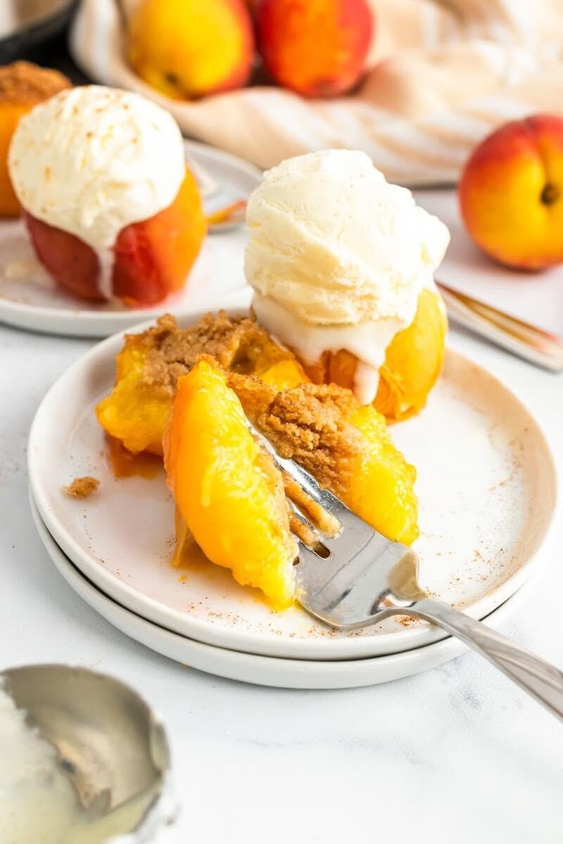 Cooked stuffed peaches sitting on plates, two topped with a scoop of vanilla ice cream, and one being cut open with a fork, sitting next to fresh peaches, an ice cream scooper and an Instant Pot.