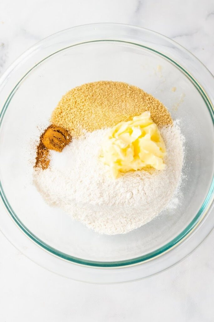 A mixing bowl full of cassava flour, maple sugar, cinnamon and butter.