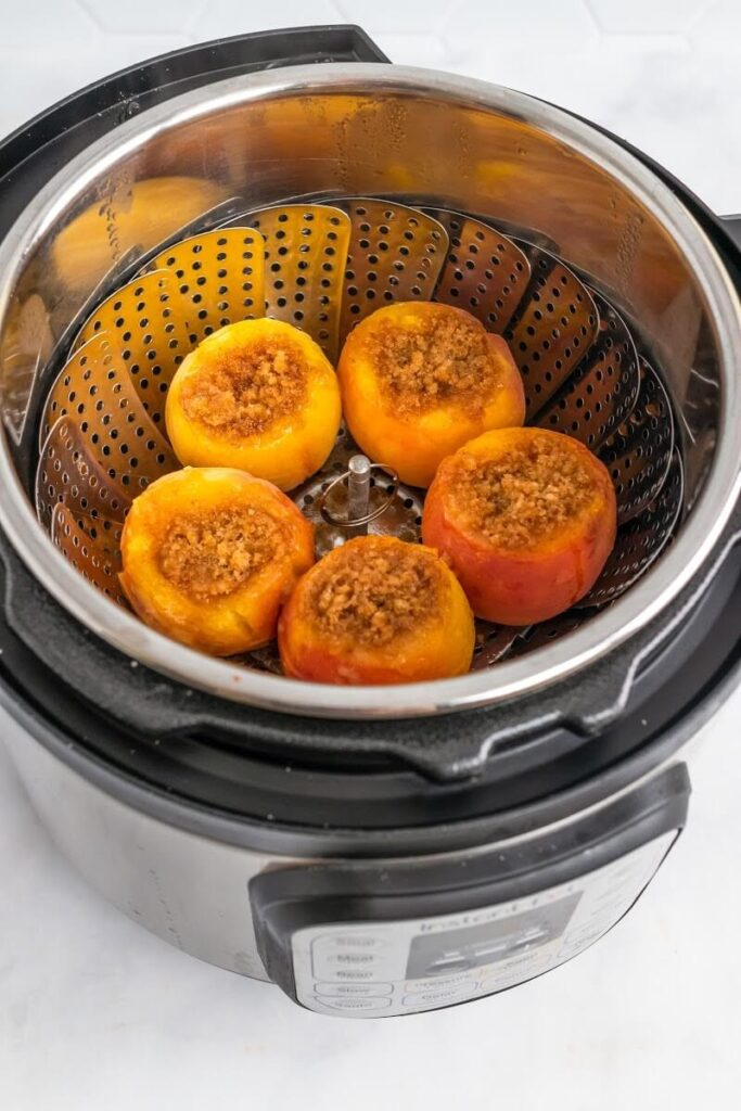 A steamer basket insert inside an Instant Pot with 5 cooked stuffed peaches sitting in the steamer basket insert.