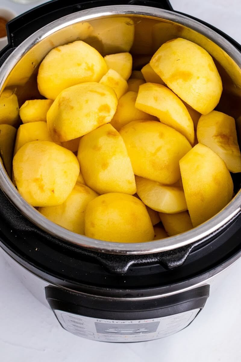 An open Instant Pot filled with quartered, peeled, fresh apples.