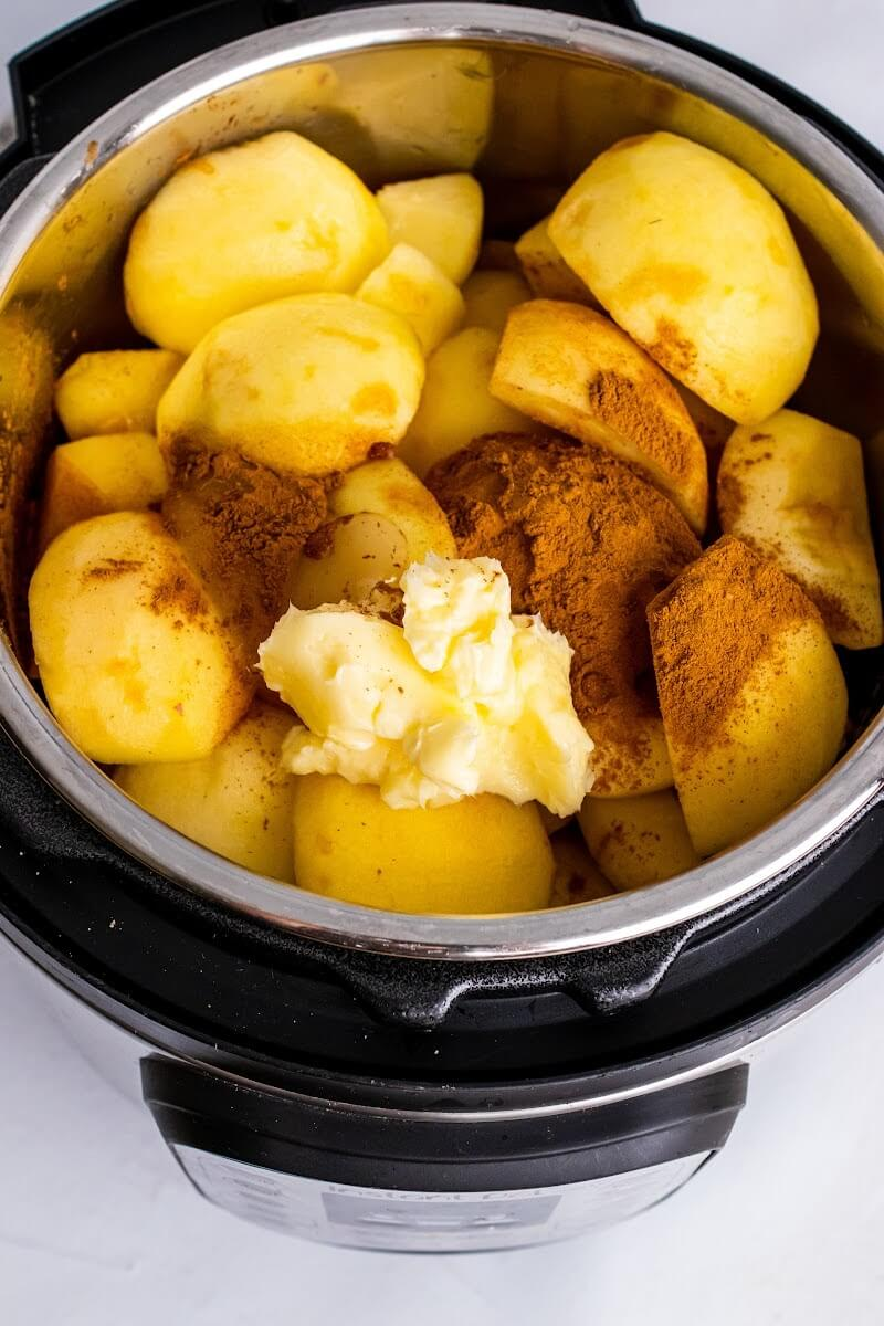 An open Instant Pot filled with quartered, peeled, fresh apples, topped with ground cinnamon and tablespoons of butter.