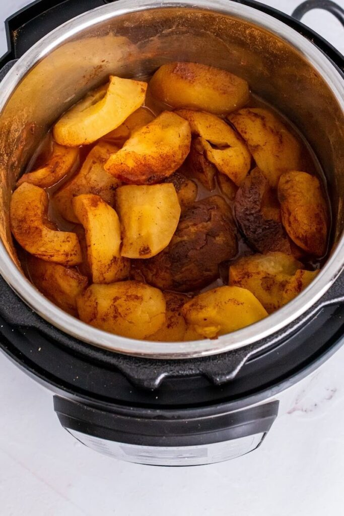An open Instant Pot filled with quartered, cooked apples in a cinnamon-filled liquid.